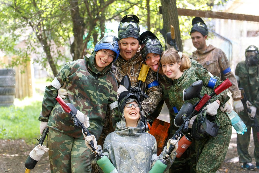 Family posing in paintball outfits